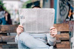 Homme assis sur un banc en bois qui lit un journal qui cache son visage